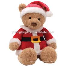 Urso de assento novo do marrom da chegada que veste a roupa do Natal