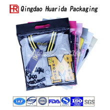 Bolsos de compras plásticos del bolso del regalo del patrón de la insignia con la bolsa de empaquetado de la ropa plástica de la manija