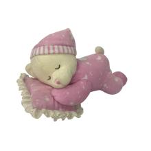 Urso de pelúcia dormindo em almofadas rosa