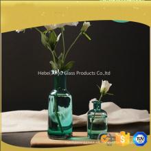 Boca ancha florero de vidrio azul para la decoración del hogar con flor