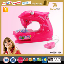 La belleza colorea el juego casero de la muchacha juguete accionado por batería de la máquina de coser a los cabritos