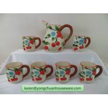 Jarra de cerámica pintada a mano del color con las tazas