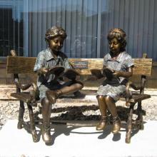 two children sitting on bench reading bronze statue sculpture