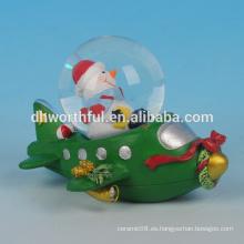 Decoración de Navidad de resina globo de nieve de Navidad con la estatuilla de muñeco de nieve en el avión