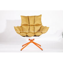 white husk chair with orange seat cushion