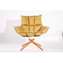 Weißer Schalenstuhl mit orangefarbenem Sitzkissen