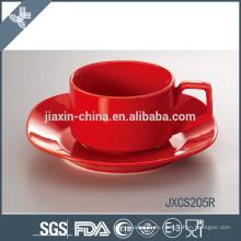 Керамическая красная чашка кофе и блюдце
