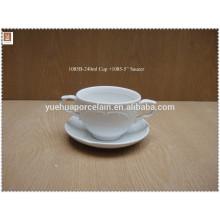Круглая белая фарфоровая чашка с двумя ручками и блюдцем