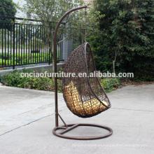 Mano que teje los muebles al aire libre que cuelgan la silla de mimbre del huevo