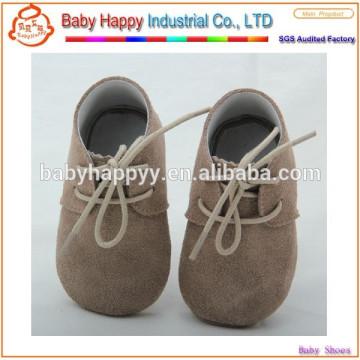 El bebé calza los zapatos del primer paso del bebé