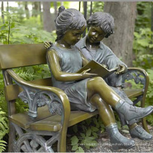 bronze boy and girl sitting on bench sculpture
