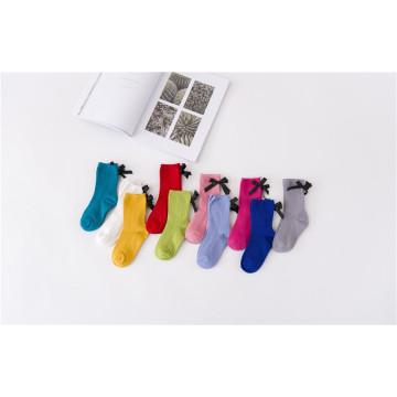 La muchacha dulce de la manera pega los colores del caramelo con los colores de los calcetines del algodón de Beatifual del arco modificados para requisitos particulares