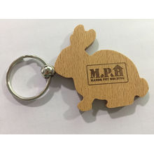 Chaveiro feito a mão de madeira da placa feita sob encomenda relativa à promoção da forma do coelho da lembrança da fábrica