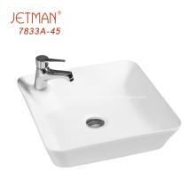 Небольшая прямоугольная белая раковина для мытья рук на столешнице