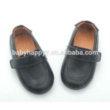 El último negro llano del estilo calza los zapatos de bebé del muchacho