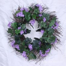 Couronnes à feuilles persistantes artificielles avec des fleurs