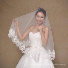 Una capa de velo de boda de marfil corto con borde ancho
