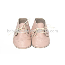 El niño de cuero de los niños bonito calza los zapatos de vestido del bebé