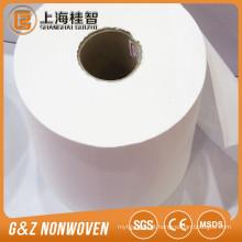 a mão e a cara limpando a tela não tecida molhada do spunlace da matéria prima do papel de tecido