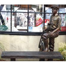escultura de bronze de tamanho de vida ao ar livre de um caddie com um banco