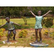 Menino de bronze do tamanho da vida dos projetos populares e menina que jogam a estátua para o jardim