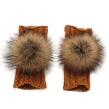Las muchachas de la manera del invierno hicieron punto los guantes con una bola de la piel del mapache