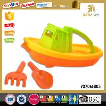 Atractivo niño juguete barco de playa con pala