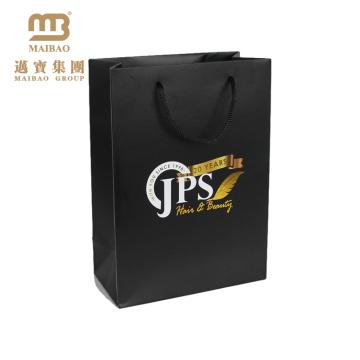 Le porte-clés de cadeau de boutique de détail empaquetant le sac à provisions en papier de luxe de conception noire faite sur commande avec le logo