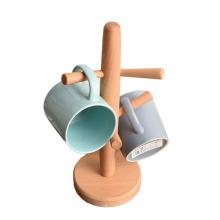 Los ganchos del árbol de la taza sostienen el portavasos de café de madera