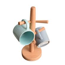 Les crochets de l'arbre à tasses contiennent un porte-gobelet à café en bois