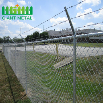Galvanized chain fence with top barbed wire