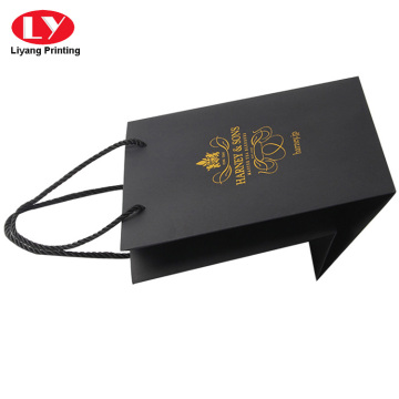 Black small paper bag printed with foil logo