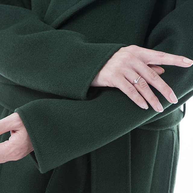 The sleeves of a green cashmere overcoat