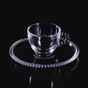 Beaded glass cup and saucer